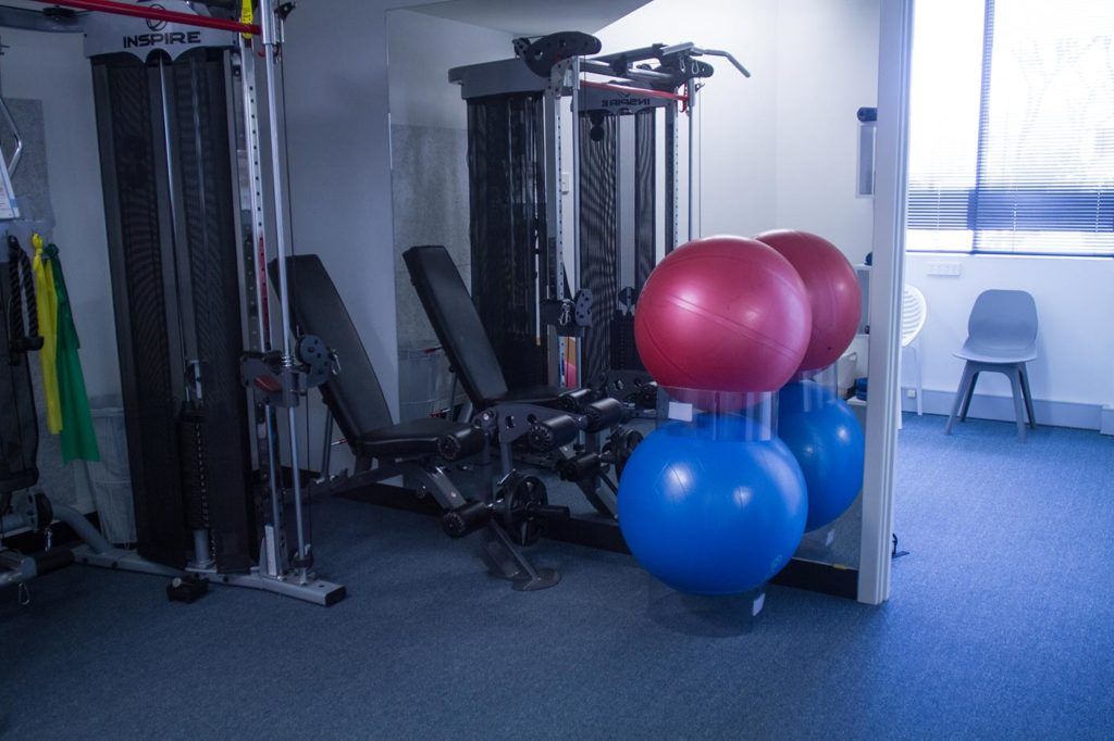 Gym facility with two yoga balls colored red and blue, 3 in 1 black bench and multi-gym machine equipment.