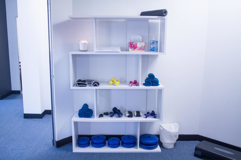 A white shelf that has blue weight plates, mini dumbbells, candle, hand sanitizer, tissue, blue towels and a barbell pad at the topmost shelf.