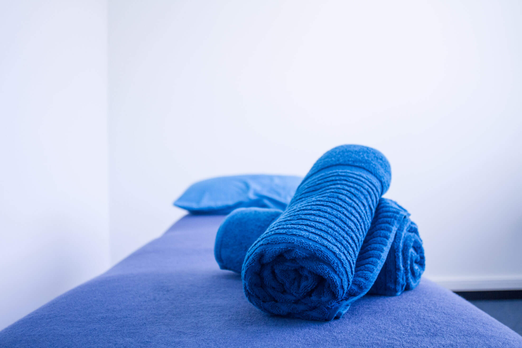 Blue colored bed with blue pillow and the rolled blue colored towel is placed on top in the bed.