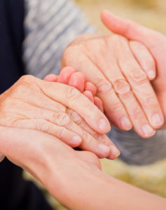A younger person is holding an elderly hands with care.