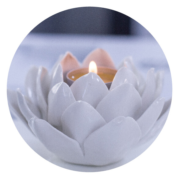 White lotus candle holder with a candle lit in the center