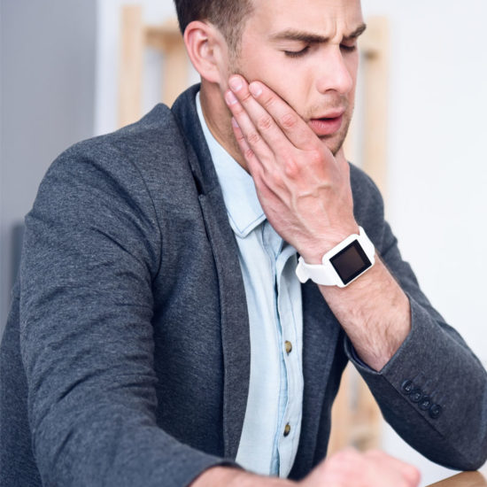 A gentleman in semi-formal attire that is holding his jaw while closing his eyes in pain.