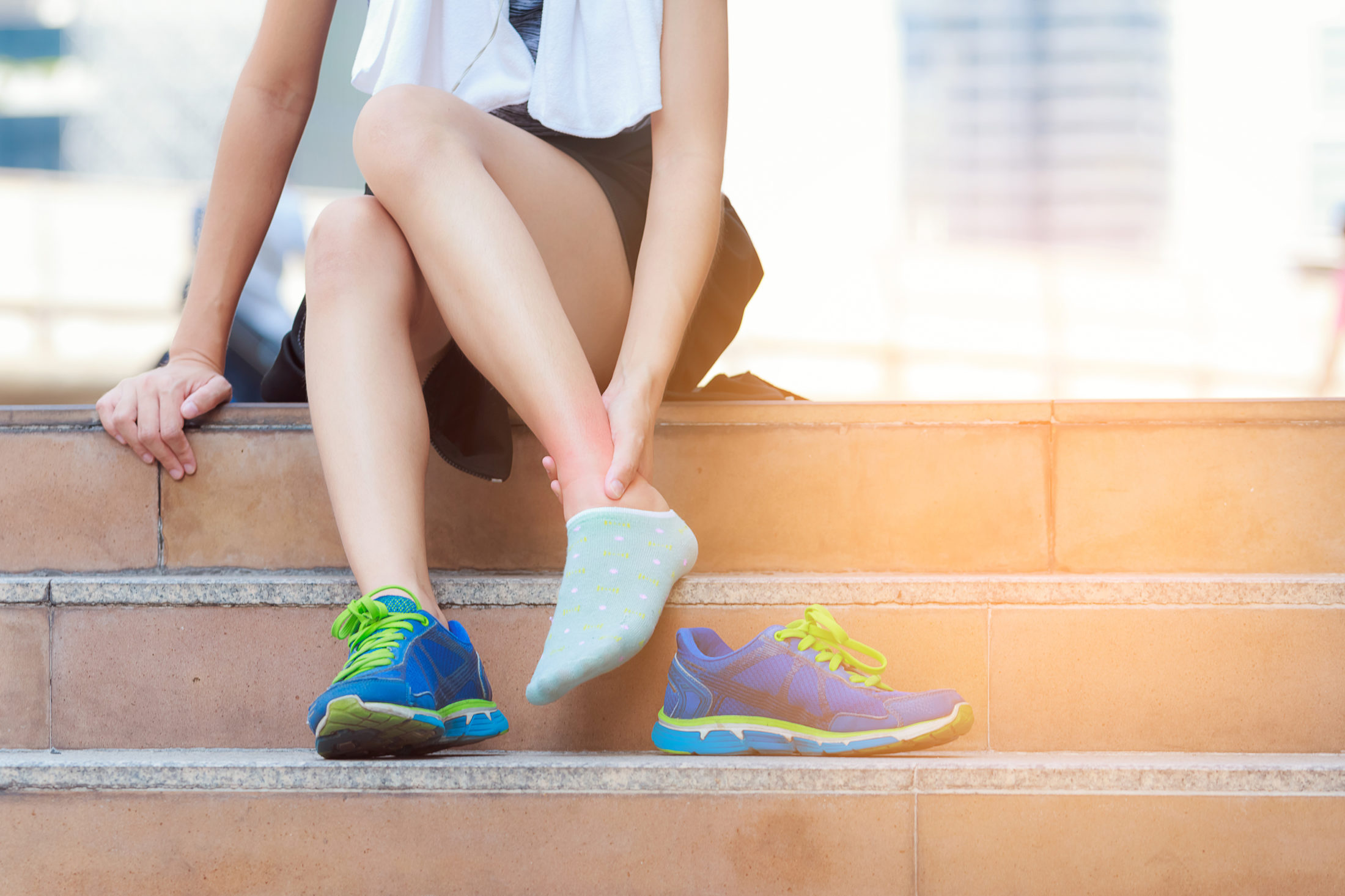 A woman that has a jacket on her waist sitting on the stairs holding her sprain ankle.