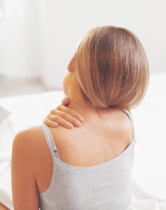A woman is wearing grey sleeveless shirt turning her back while reaching her neck in pain.