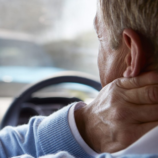 An old man is wearing a sweater that is color light blue and driving while holding his nape in pain.