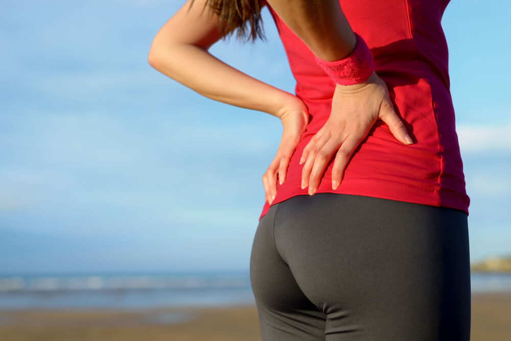 Woman experiencing hip pain while running