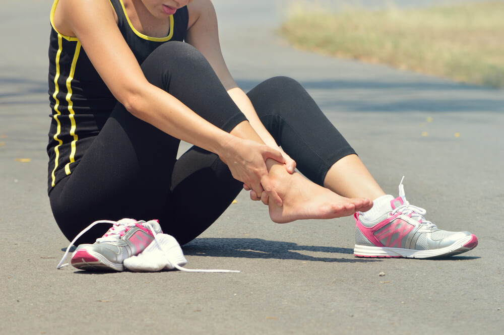 Woman with sprained ankle while exercising and running
