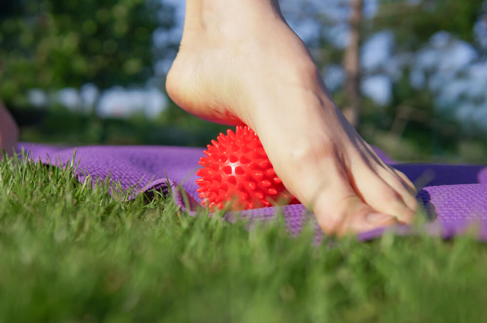 Doing a foot exercise with a spiky ball