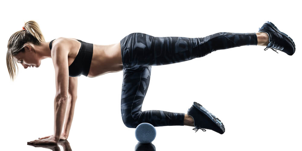 Woman doing an anterior chain exercise with foam rollers