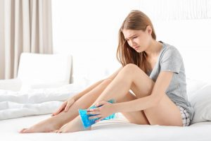 Woman putting ice pack on her sprained ankle