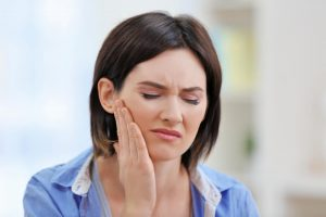 A young woman experiencing jaw pain
