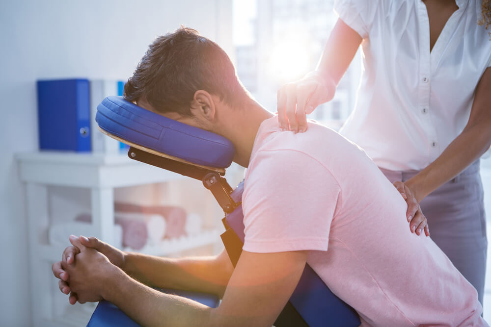 Man having his back checked by a physiotherapy