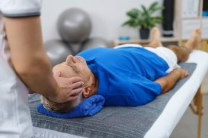 Old man having a head and neck physio therapy