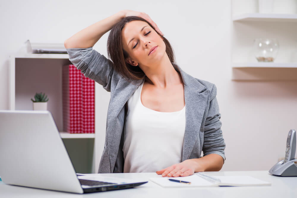 Woman stretching her neck while in the office