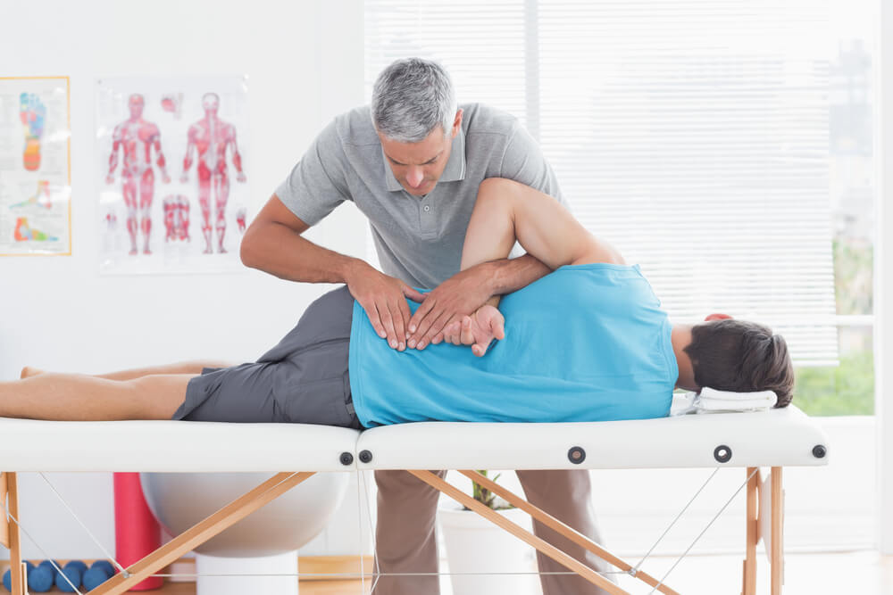 A physiotherapist checking the back of the patient