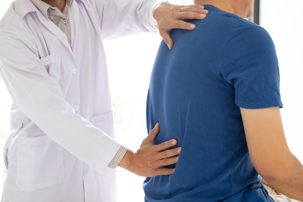 Man suffering from back pain being checked by a physio